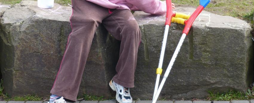 Infant amb discapacitat assegut. Al costat hi ha unes muletes.