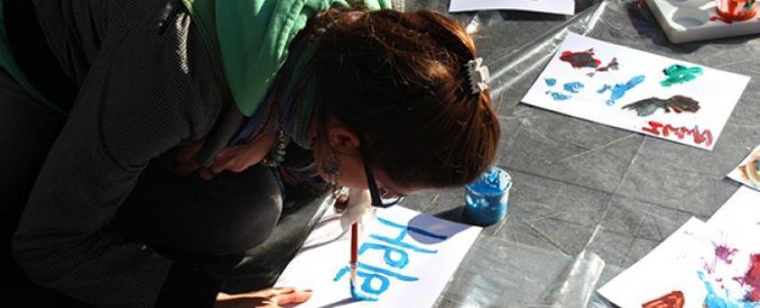 Imatge d'una noia pintant amb un pinzell a la boca. Imatge d'arxiu.
