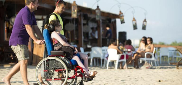 Dos nois acompanyant una noia en cadira de rodes a la platja