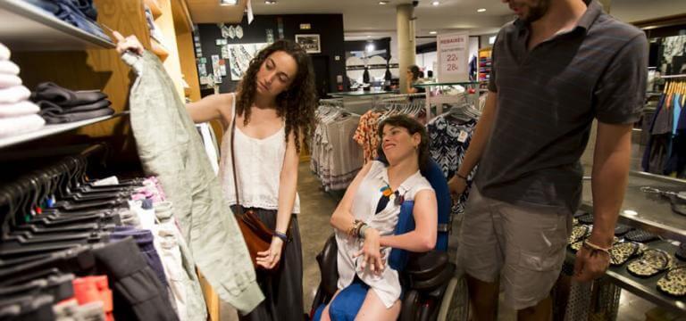 Una noia i un noi comprant a una botiga de roba amb una noia en cadira de rodes