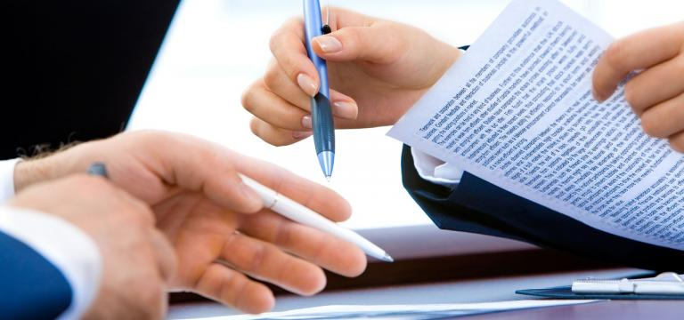 Primer plano de dos manos de dos personas diferentes con papel i bolígrafos en las manos comi si estuvieran comparando información