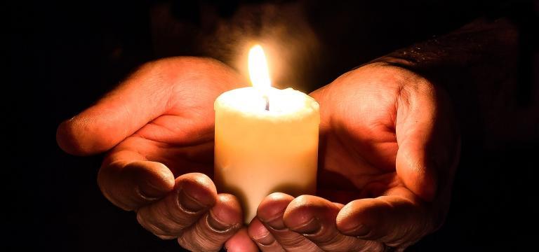 Dos manos en posición de ofrecimiento, sosteniendo, ofreciendo una vela