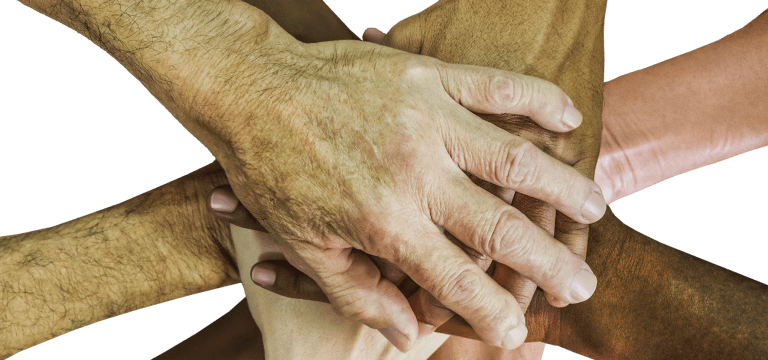 Un grupo de manos de diferentes personas, unas sobre las otras