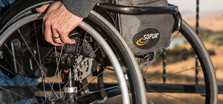Primer plano de las ruedas de una silla de ruedas; en una de las ruedas se ve la mano de la persona que está sentada en ella
