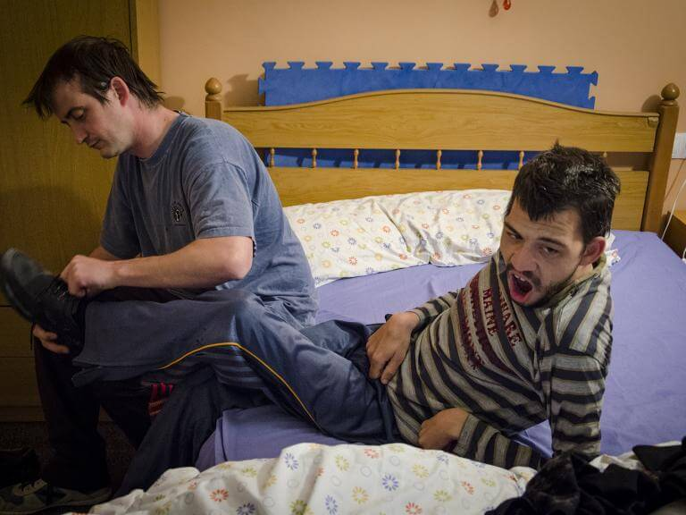 Dues persones assegudes en un llit, una d'elles (que té discapacitat) està una mica recolzada enrere mentre l'altra li està posant les sabates