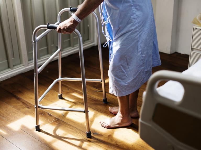 Se ve una persona de espaldas (sólo de medio tronco para abajo) junto a una cama y apoyada en un andador