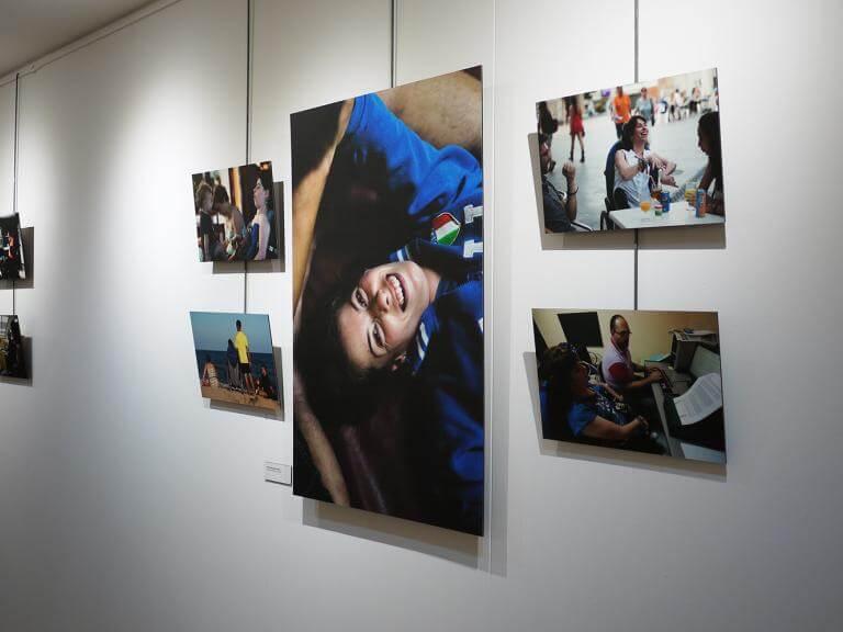 Imatge d'una paret amb diferents fotografies de l'exposició 'Vides Diverses' exposades