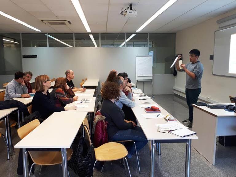 Una aula de formació amb un professor en front dels pupitres on hi ha assegut l'alumnat