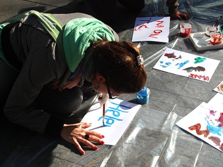 Una noia de genolls a terra intentant escriure sobre un paper el seu nom amb un pinzell posat a la boca