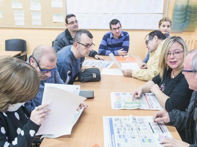 Diverses persones amb discapacitat consultant anuncis de feina a la premsa