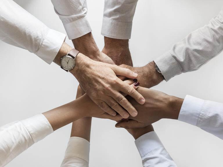 Las manos de varias personas puestas una encima de otra, como suma de esfuerzos