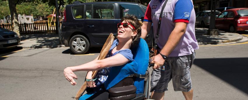 Una chica con discapacidad física cruzando la calle acompañada por su asistente personal