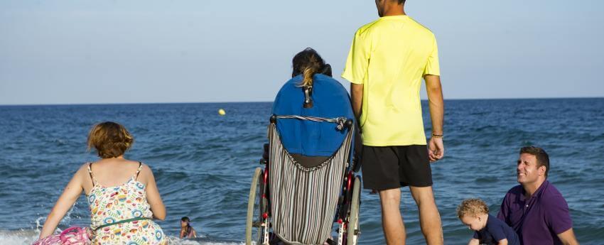 Una persona usuaria de silla de ruedas en la playa, acompañada por su asistente personal y otras personas