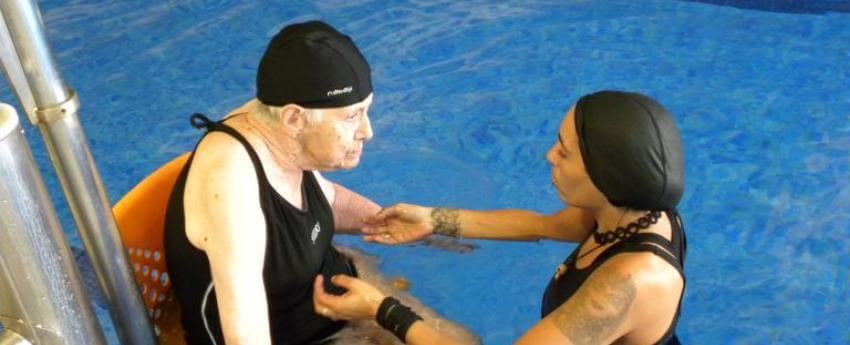 Imatge d'una noia ajudant a un usuari del servei a la piscina