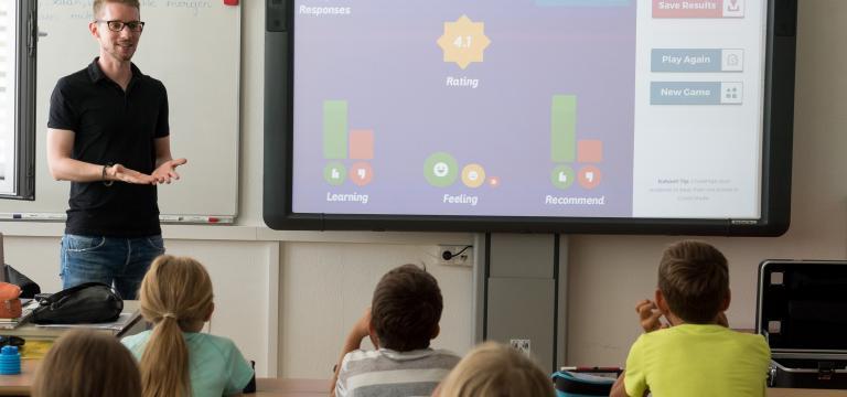 Una aula donde se ven alumnos atendiendo las explicaciones de un profesor junto a una pizarra