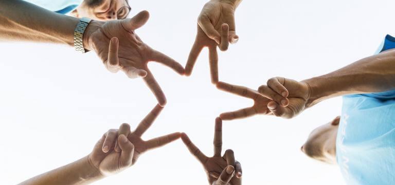 Imagen de 5 manos. Cada mano junta dos dedos con la mano de al lado y entre todos conforman una estrella
