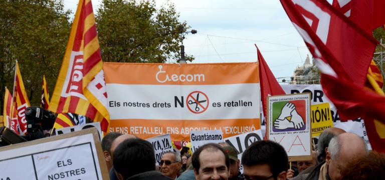 Primer plano de una pancarta reivindicativa de ECOM en una manifestación