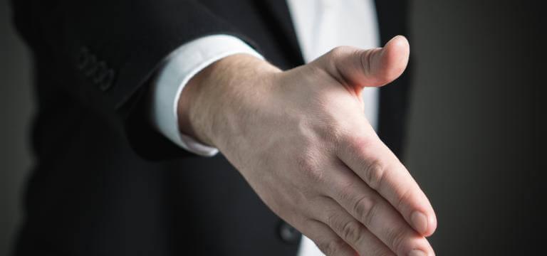 Primer plano de una mano que podría ser de un empresario (va vestido con traje). La mano está en actitud de ofrecer amistad o cerrar un trato