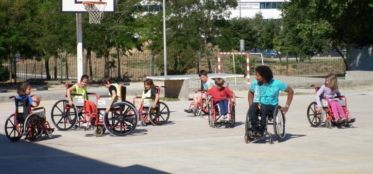 Un grupo de alumnos/as en el patio del colegio, en la cancha de baloncesto, sentados en sillas de ruedas, atendiendo las explicaciones que les está dando un chico con discapacidad (usuario de silla de ruedas) sobre cómo manejar la silla