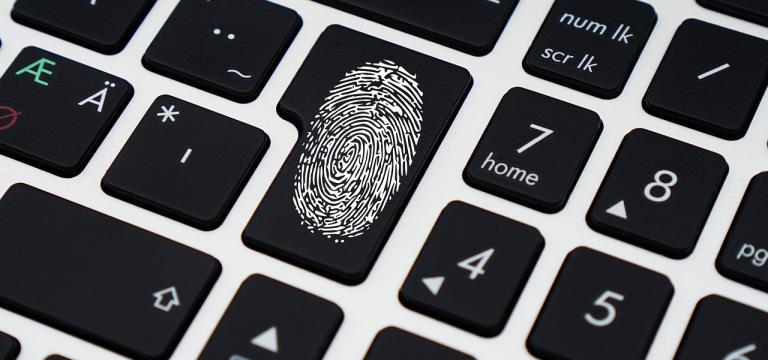 Imagen de un teclado, en que una de las teclas tiene una huella dactilar