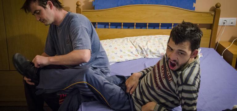 Un home ajudant a un noi a vestir-se al llit estant