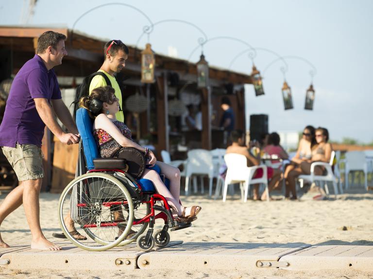 Dos chicos y una chica (con discapacidad y usuaria de silla de ruedas) están acercándose al mar avanzando sobre la plataforma de madera instalada sobre la arena para facilitar el acceso
