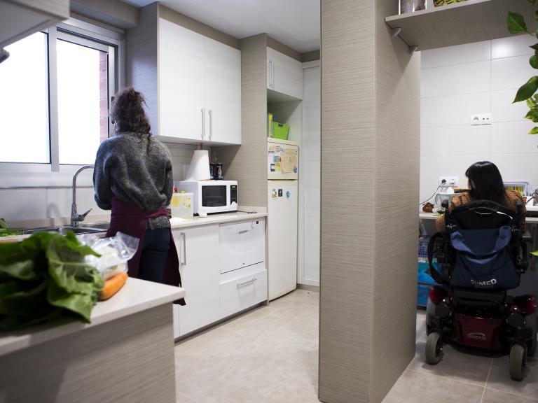 Dues dones d'esquenes (una d'elles usuària de cadira de rodes) en una cuina preparant alguna cosa de menjar sobre els marbres