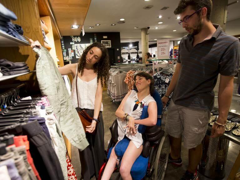 Un chico y dos chicas en una tienda de ropa, una de ellas usuaria de silla de ruedas. Están mirando ropa, una de las chicas le muestra una pieza de ropa a la otra (que tiene una discapacidad) para que ésta opine y elija.