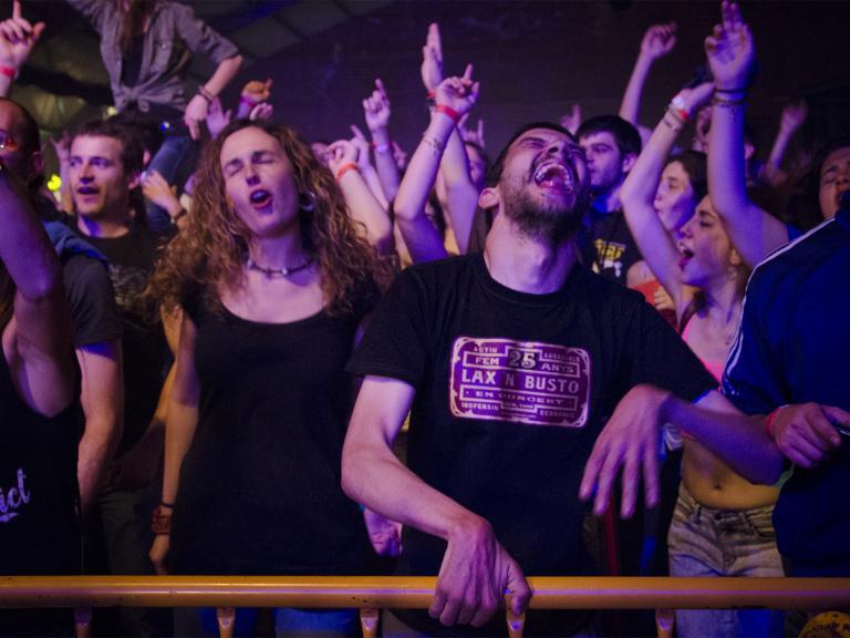 Gent jove ballant i amb els braços alçats, rera una tanca de seguretat, gaudint d'un concert. En primera fila un jove amb paràlisi cerebral