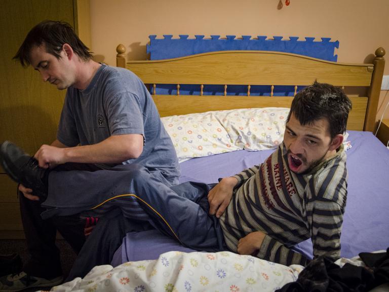 Dos personas sentadas en una cama, una de ellas (que tiene discapacidad) está un poco apoyada atrás mientras la otra le está poniendo los zapatos