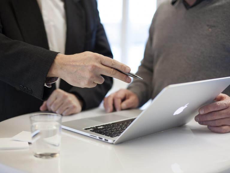 Dos homes mirant un ordinador, un d'ells en actitud d'estar explicant quelcom a l'altre