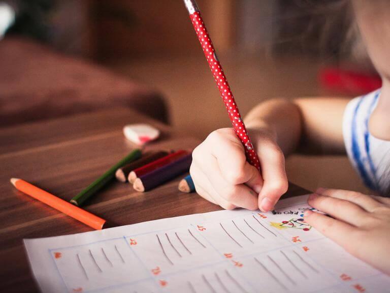 Una nena (de la qual només es veu una mica el perfil) escrivint en un paper sobre una taula on hi ha diversos llapisos