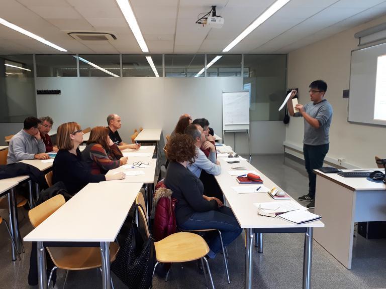 Una aula de formación con un profesor en frente de los pupitres donde está sentado el alumnado