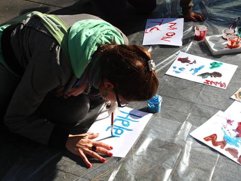 Una chica de rodillas en el suelo intentando escribir sobre un papel su nombre con un pincel puesta en la boca.