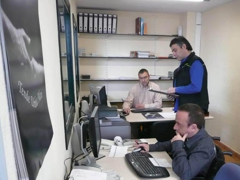 Tres personas en un despacho trabajando, una de ellas usuaria de silla de ruedas, que está trabajando con el ordenador