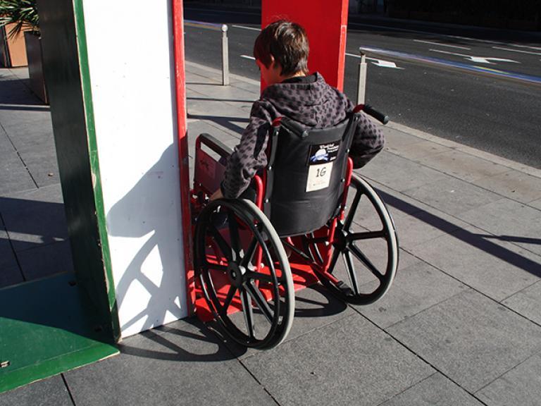 Un noi assegut en una cadira de rodes intentant passar per una estructura que simula l'entrada d'una porta. La imatge mostra dues opcions d'entrada (o porta) una pintada de verd, que és accessible, i una de vermella (que és massa estreta, tot i que permet el pas).