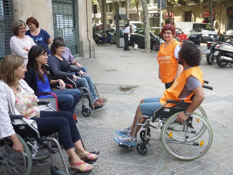 Dos tècnics d'ECOM (un d'ells assegut en una cadira de rodes) dona explicacions a professionals d'una empresa que estan assegudes en cadires de rodes preparades a fer una ruta pel carrer d'una ciutat